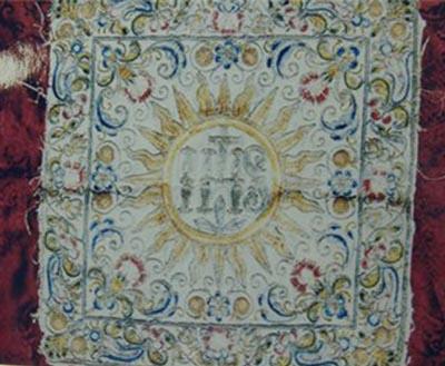 Не менее удивительным предметом является и кусок ткани, в которую был завёрнут Камень. Внутри круга Солнца располагаются латинские буквы «I.Н.S.», являющиеся начальными для надписи